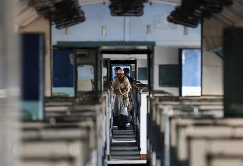 A passenger walks through a parked train carriage at a railway station in Ahmedabad June 21, 2014. REUTERS/Amit Dave