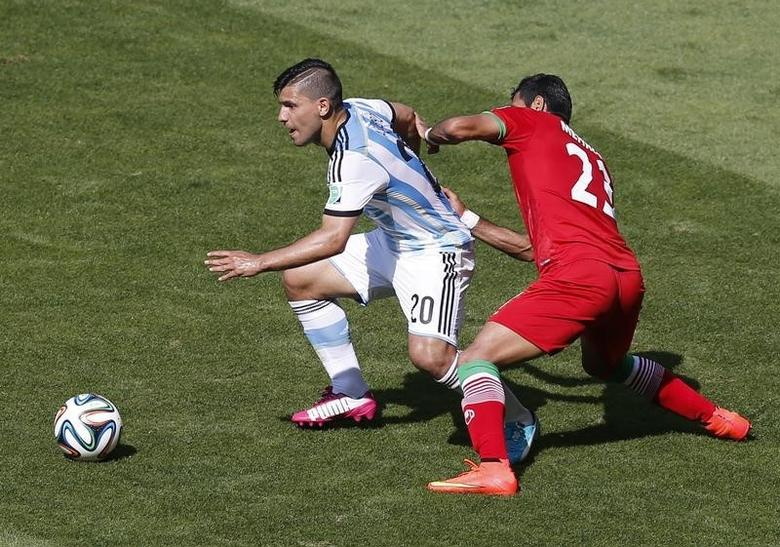 Argentina's Sergio Aguero fights for the ball against Iran's Mehrdad Pouladi during their 2014 World Cup Group F soccer match at the Mineirao stadium in Belo Horizonte June 21, 2014. REUTERS/Leonhard Foeger