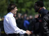 Belgium's Prime Minister Elio Di Rupo (L) shakes hands with Belgium's soccer player Romelu Lukaku during a training session at the squad's camp ahead of the World Cup, in Knokke-Heist June 5, 2014.   REUTERS/Eric Vidal