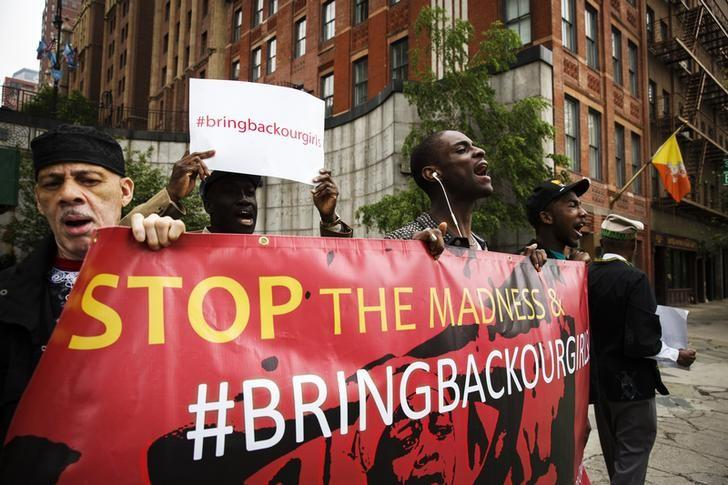 Demonstrators hold signs while chanting for the release of the Nigerian schoolgirls in Chibok who were kidnapped by Islamist militant group Boko Haram, outside of United Nations headquarters in New York, May 22, 2014.  REUTERS/Lucas Jackson