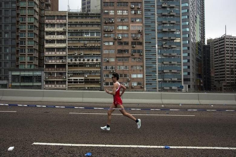 A participant runs past a old residential zone on the Connaught Road West Flyover as he competes in the Hong Kong marathon February 16, 2014. REUTERS/Tyrone Siu
