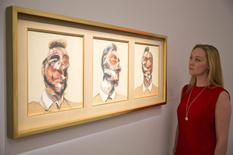 A gallery assistant views the work Three Studies for George Dyer (on a light background) by Francis Bacon at a photo-call for Impressionist and Modern Art Evening Sale at Sotheby's auction house in London June 18, 2014. REUTERS/Neil Hall