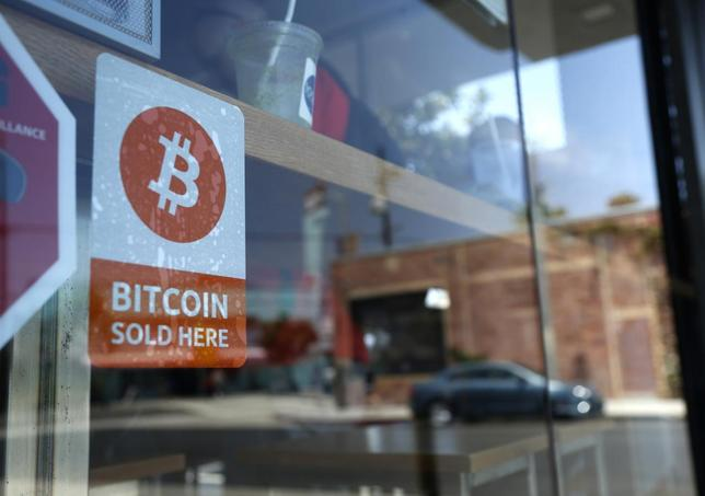 A bitcoin sticker is seen in the window of Locali Conscious Convenience store, where one of Southern California's first two bitcoin-to-cash ATMs began operating in Venice, Los Angeles, California, June 21, 2014. REUTERS/Lucy Nicholson