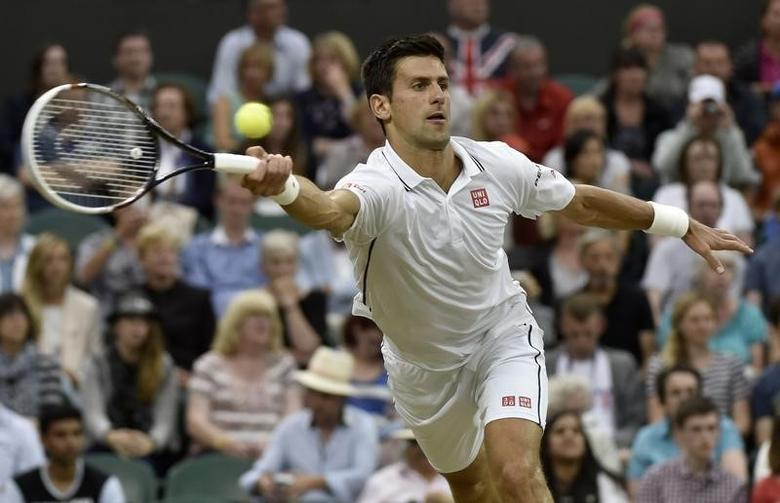 Novak Djokovic of Serbia hits a return to Jo-Wilfried Tsonga of France during their men's singles tennis match at the Wimbledon Tennis Championships, in London June 30, 2014.              REUTERS/Toby Melville