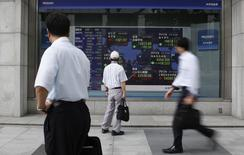 En la imagen, transeúntes miran a un panel electrónico en el que se muestran varios índices bursátiles en una casa de bolsa en Tokio el 25 de junio de 2014.  Las bolsas de Asia subieron el miércoles a unos máximos en tres años gracias a unos datos optimistas sobre la economía mundial que estimulaban el apetito por el riesgo y ayudaron a Wall Street a tocar unos máximos históricos. REUTERS/Yuya Shino