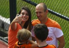 Netherlands' national soccer team player Arjen Robben poses for a photo with a fan after a training session in Rio de Janeiro, July 2, 2014. REUTERS/Pilar Olivares