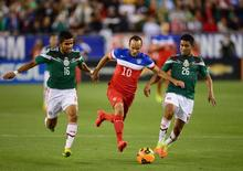 USA midfielder Landon Donovan (10) controls the ball against Mexico defender Miguel Ponce (16) and midfielder Juan Medina (26) in the second half during a friendly match at University of Phoenix Stadium. Apr 2, 2014.Justin Tooley-USA TODAY Sports - RTR3JQEJ