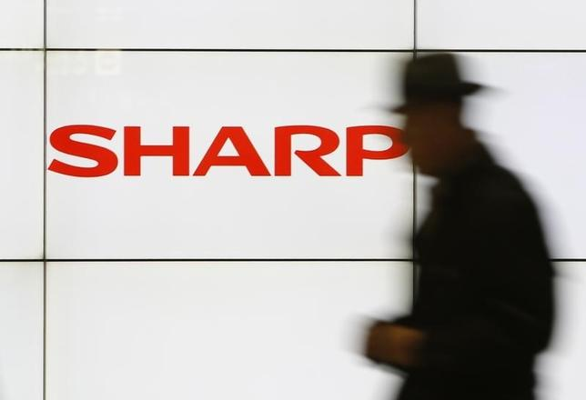 A pedestrian walks past a logo of Sharp Corp at a train station in Tokyo February 3, 2014. REUTERS/Yuya Shino/Files