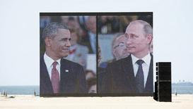 Президент США Барак Обама (слева) и президент России Владимир Путин на экране во время празднования юбилея высадки союзников в Уистреаме 6 июня 2014 года. Президент России Владимир Путин выразил надежду на развитие отношений с США, поздравив своего американского коллегу Барака Обаму с Днем независимости США. REUTERS/Kevin