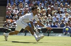 Novak Djokovic of Serbia hits a return during his men's singles semi-final tennis match against Grigor Dimitrov of Bulgaria at the Wimbledon Tennis Championships, in London July 4, 2014.        REUTERS/Toby Melville