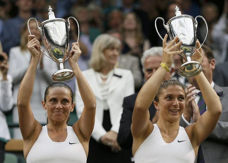 Sara Errani of Italy (R) and Roberta Vinci of Italy celebrate with their winners trophies after defeating Timea Babos of Hungary and Kristina Mladenovic of France in their women's doubles tennis match at the Wimbledon Tennis Championships, in London July 5, 2014.  REUTERS/Stefan Wermuth