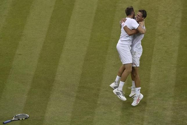 Vasek Pospisil of Canada and Jack Sock of the U.S. (L) celebrate defeating Bob Bryan of the U.S. and Mike Bryan of the U.S. in their men's doubles final tennis match at the Wimbledon Tennis Championships, in London July 5, 2014.           REUTERS/Toby Melville