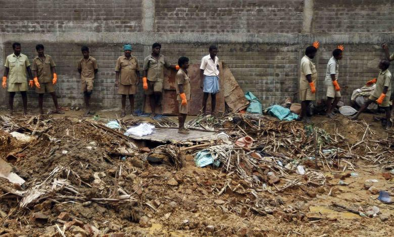 Municipality workers stand at the site of a collapsed compound wall of a warehouse on the outskirts of the southern Indian city of Chennai July 6, 2014.  REUTERS/Babu