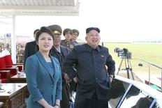 North Korean leader Kim Jong Un (R) stands next to his wife Ri Sol Ju as they attend the 2014 Combat Flight Contest among commanding officers of the Korean People's Air Force in this undated photo released by North Korea's Korean Central News Agency (KCNA) in Pyongyang May 10, 2014. REUTERS/KCNA