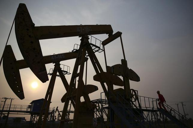 A worker examines a pumpjack at a PetroChina oil field in Panjin, Liaoning province June 30, 2014.  REUTERS/Sheng Li