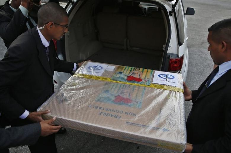 A box containing a painting of French master Henri Matisse, known as ''Odalisque in Red Pants'' (Odalisque a la Culotte Rouge), is moved into a car after arriving at Maiquetia International Airport in Caracas July 7, 2014. REUTERS/Carlos Garcia Rawlins