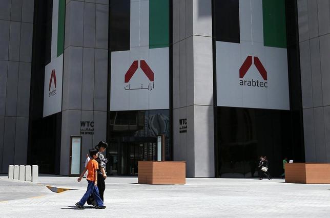 People walk past the Arabtec headquarters in Abu Dhabi June 25, 2014.   REUTERS/Stringer