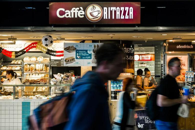 People walk past a Caffe Ritazza outlet at the central train station in Berlin, June 17, 2014.  REUTERS/Thomas Peter