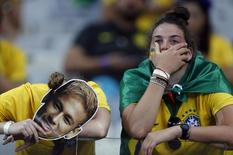 Fans of Brazil react after their loss to Germany in their 2014 World Cup semi-finals at the Mineirao stadium in Belo Horizonte July 8, 2014. REUTERS/Marcos Brindicci (BRAZIL  - Tags: SOCCER SPORT WORLD CUP)