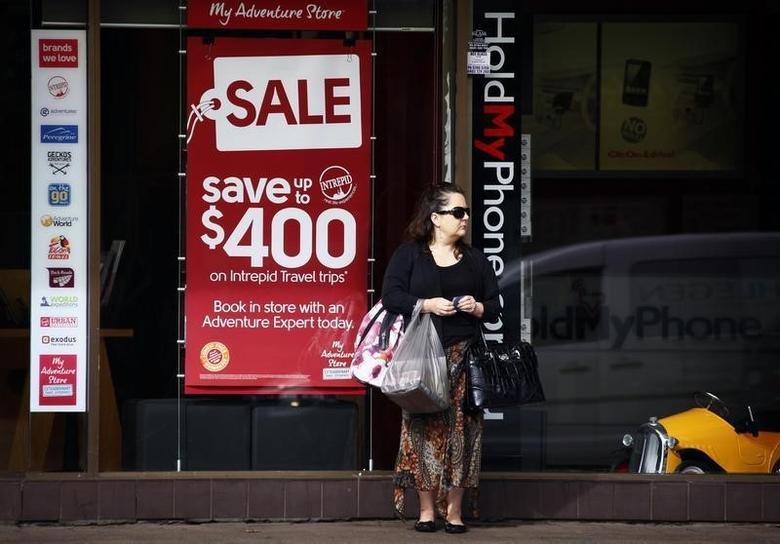 A woman holds shopping bags as she stands outside a store on a main street in Sydney April 30, 2014.   REUTERS/David Gray