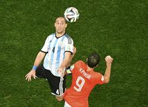 Argentina's Pablo Zabaleta is challenged by Robin van Persie of the Netherlands (R) during extra time in their 2014 World Cup semi-finals at the Corinthians arena in Sao Paulo July 9, 2014. REUTERS/Francois Xavier Marit/Pool