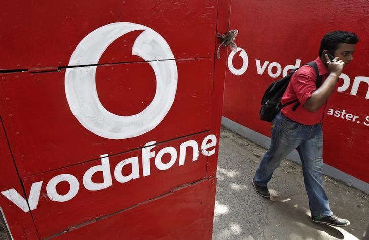 A man speaks on his mobile phone as he walks past logos of Vodafone painted on a roadside wall in Kolkata May 20, 2014. REUTERS/Rupak De Chowdhuri