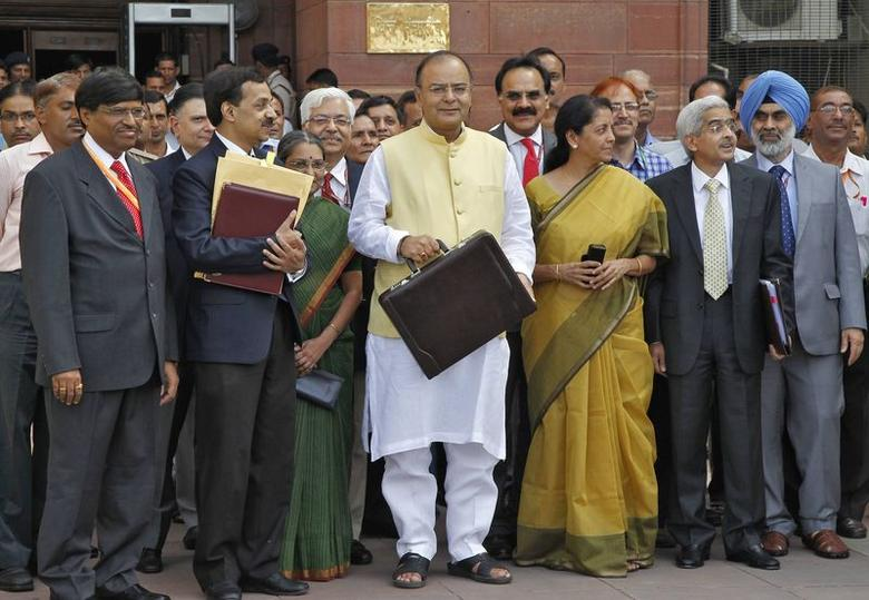Finance Minister Arun Jaitley (C) poses as he leaves his office to present the budget for the 2014/15 fiscal year, in New Delhi July 10, 2014. REUTERS/Stringer
