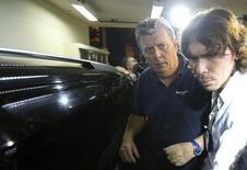 Executivo da Match Ray Whelan (E) chega à polícia suspeito de envolvimento em venda ilegal de ingressos para a Copa. 7/7/2014 REUTERS/Stringer