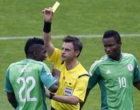 Árbitro Nicola Rizzoli mostra cartão para jogador da Nigéria Kenneth Omeruo (E) em partida no Beira-Rio, em Porto Alegre. 25/6/2014. REUTERS/Marko Djurica