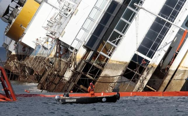 Salvage crew workers are seen in front of the capsized Costa Concordia cruise liner after the start of the ''parbuckling'' operation outside Giglio harbour September 16, 2013.  REUTERS/ Tony Gentile