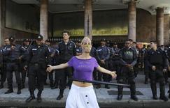 Mulher faz ato em frente a contigente policial antes de partida entre Argentina e Alemanha pela final da Copa do Mundo, no Rio de Janeiro. 13/7/2014 REUTERS/Nacho Doce