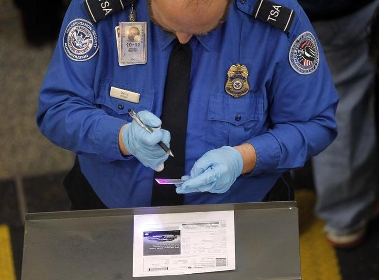 A Transportation Security Administration (TSA) agent uses a special light to check the authenticity of a traveller's driver's license at Ronald Reagan Washington National Airport in Washington November 24, 2010. REUTERS/Jason Reed