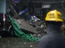 """Спасатель у обрушившегося здания в Кесон-Сити 16 июля 2014 года. Число жертв мощного тайфуна """"Раммасун"""", пронесшегося через Филиппины, выросло до 38 человек, еще по меньшей мере восемь человек считаются пропавшими без вести, сообщили чрезвычайные службы страны. REUTERS/Al Falcon"""
