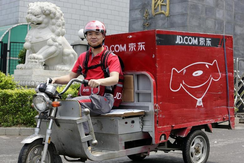 Richard Liu, CEO and founder of China's e-commerce company JD.com, rides an electric tricycle as he leaves a delivery station to deliver goods for customers to celebrate the anniversary of the founding of the company, in Beijing, June 16, 2014.  REUTERS/Jason Lee