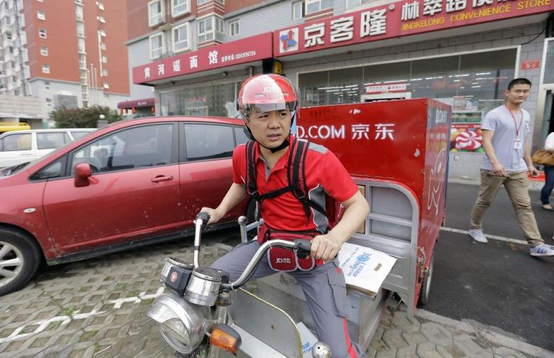 Richard Liu, CEO and founder of China's e-commerce company JD.com, rides an electric tricycle as he leaves a delivery station to deliver goods for customers to celebrate the anniversary of the founding of the company, in Beijing, June 16, 2014. REUTERS/Jason Lee/Files