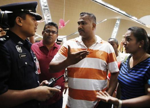 People, who said they believed their relatives were on Malaysia Airlines flight MH17, speak to a police officer for more information about the crashed plane at Kuala Lumpur International Airport in Sepang July 18, 2014. REUTERS/Olivia Harris