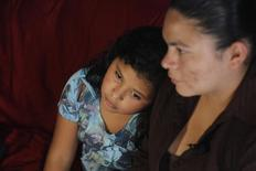 Victoria Cordova and her daughter Genesis Zepeda, both recently deported from the U.S., sit at their home at the impoverished 21 de Marzo neighbourhood in Tegucigalpa July 15, 2014. REUTERS/Jorge Cabrera