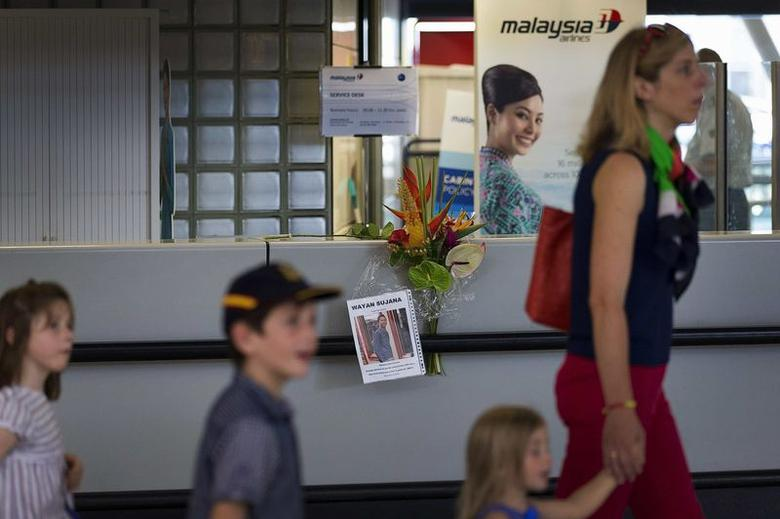 A mother with her children walks past a Malaysia Airlines counter where flowers were placed by someone, at Schiphol Airport July 18, 2014. REUTERS/Michael Kooren
