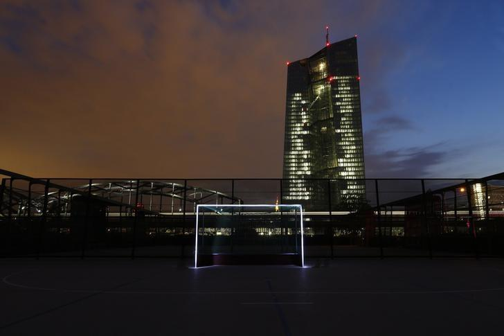 A photograph taken using long exposure shows a goalpost which has been illuminated with torches at a leisure facility in front of the European Central Bank (ECB) headquarters in Frankfurt June 1, 2014. REUTERS/Ralph Orlowski