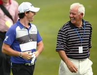 Rory McIlroy of Northern Ireland (L), laughs with his father, Gerry as they walk down the fairway during a practice round in preparation for this week's PGA Championship golf tournament at The Ocean Course on Kiawah Island, South Carolina, August 7, 2012. REUTERS/Chris Keane