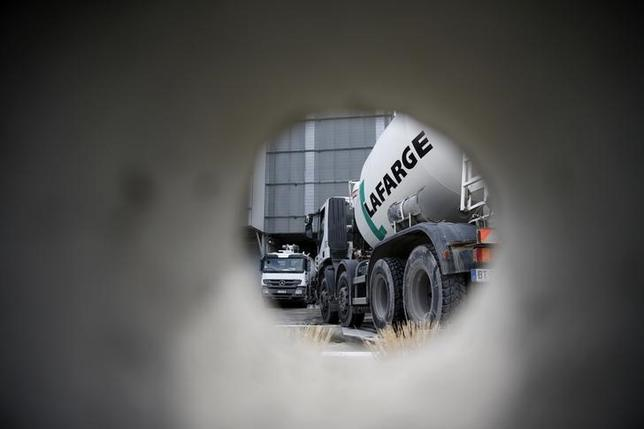A concrete mixing truck is seen through a hole in a wall at Lafarge concrete production plant in Pantin, outside Paris, April 7, 2014.  REUTERS/Christian Hartmann
