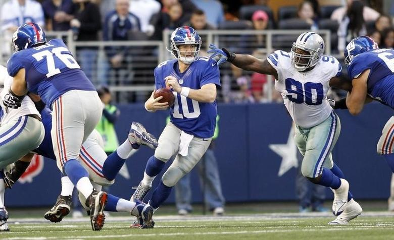 New York Giants quarterback Eli Manning scrambles from the pocket as guard Chris Snee (L) blocks and nose tackle Jay Ratliff (R) pursues in the first half of their NFL football game in Arlington, Texas October 28, 2012. REUTERS/Mike Stone