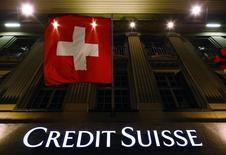 Логотип Credit Suisse и флаг Швейцарии на здании в Берне 15 мая 2014 года. Credit Suisse Group AG отчитался о максимальных квартальных убытках с обвала Lehman Brothers в 2008 году, причиной которых стала выплата 1,6 миллиарда швейцарских франков ($1,78 миллиарда) властям США для урегулирования обвинений в уклонении от налогов. REUTERS/Ruben Sprich