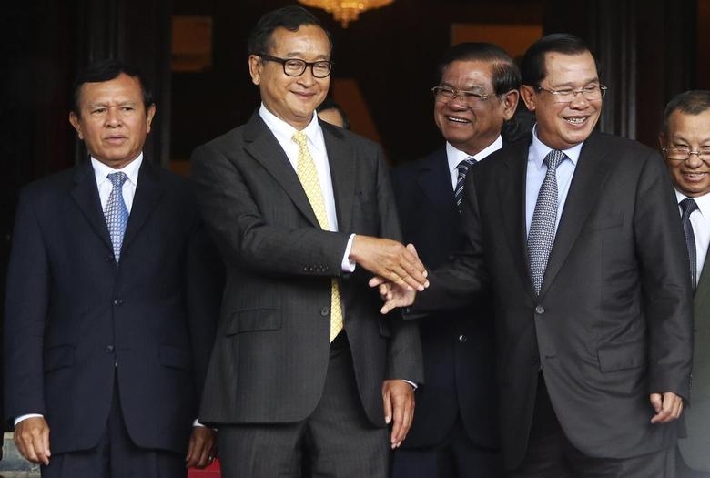 Cambodia's Prime Minister Hun Sen (2nd R) shakes hands with Sam Rainsy (2nd L), president of the Cambodia National Rescue Party (CNRP), after a meeting at the Senate in central Phnom Penh July 22, 2014. REUTERS/Stringer