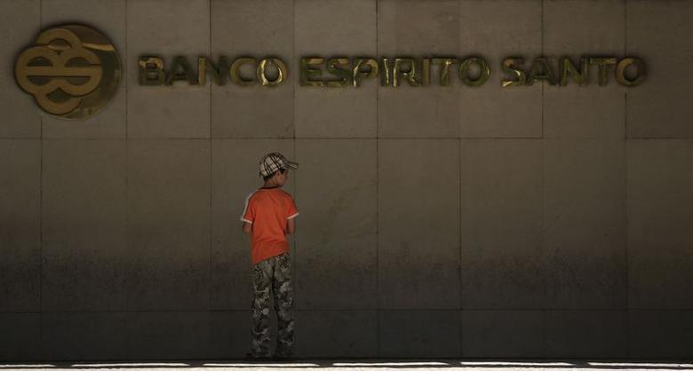 A boy stands in front of the logo of Portuguese bank Banco Espirito Santo (BES), which is partially controlled by the Espirito Santo family, at the bank's headquarters in Lisbon July 16, 2014.  REUTERS/Rafael Marchante