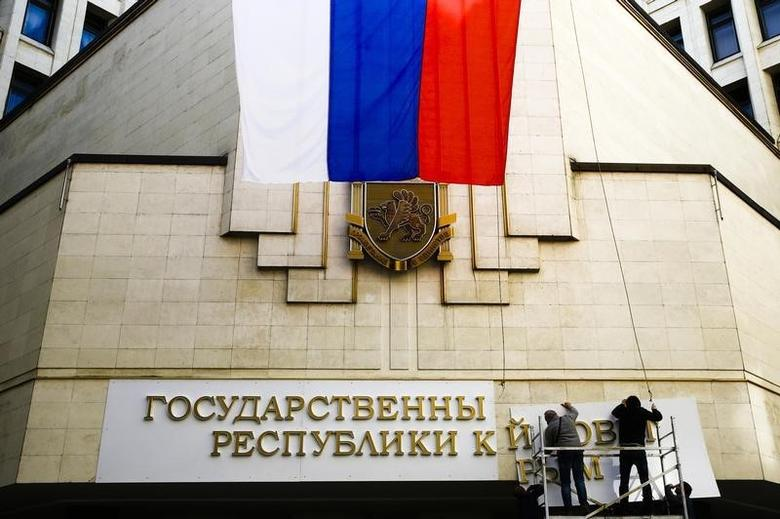 Workers put up a new sign at the local parliament building in Simferopol March 19, 2014.   REUTERS/Thomas Peter