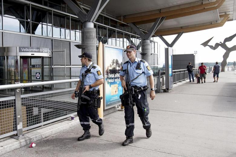 Armed police officers patrol outside a terminal building at Oslo Airport July 24, 2014. REUTERS/Audun Braastad/NTB Scanpix