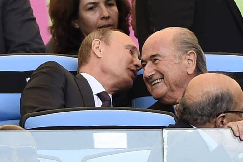 Russian President Vladimir Putin (L) speaks to FIFA President Sepp Blatter during the 2014 World Cup final between Germany and Argentina at the Maracana stadium in Rio de Janeiro July 13, 2014. REUTERS/Dylan Martinez