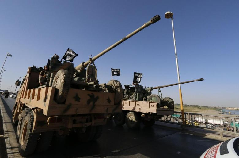 Militant Islamist fighters travel in a vehicle as they take part in a military parade along the streets of Syria's northern Raqqa province June 30, 2014 file photo.REUTERS/Stringer