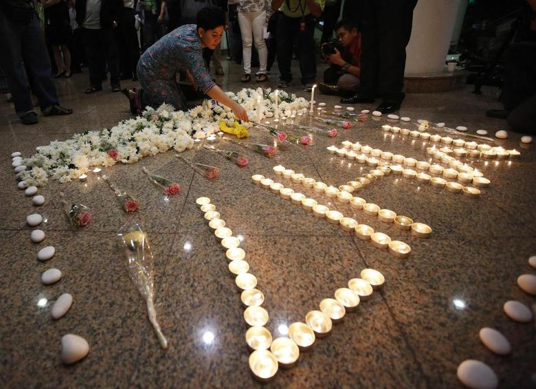 A stewardess from Malaysia Airlines lays a flower in remembrance of lost colleagues during a multi-faith event to pray for the passengers and crew of MH17 at the airline's academy in Kuala Lumpur July 25, 2014.  REUTERS/Olivia Harris